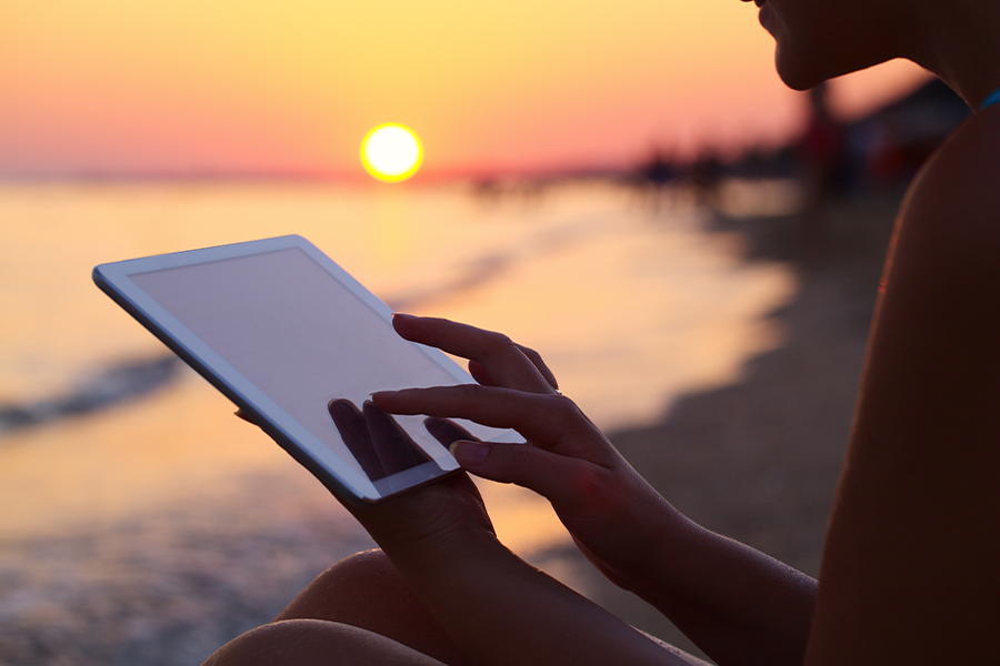 Client Center - Woman Using iPad Outdoors on the Beach at Sunset